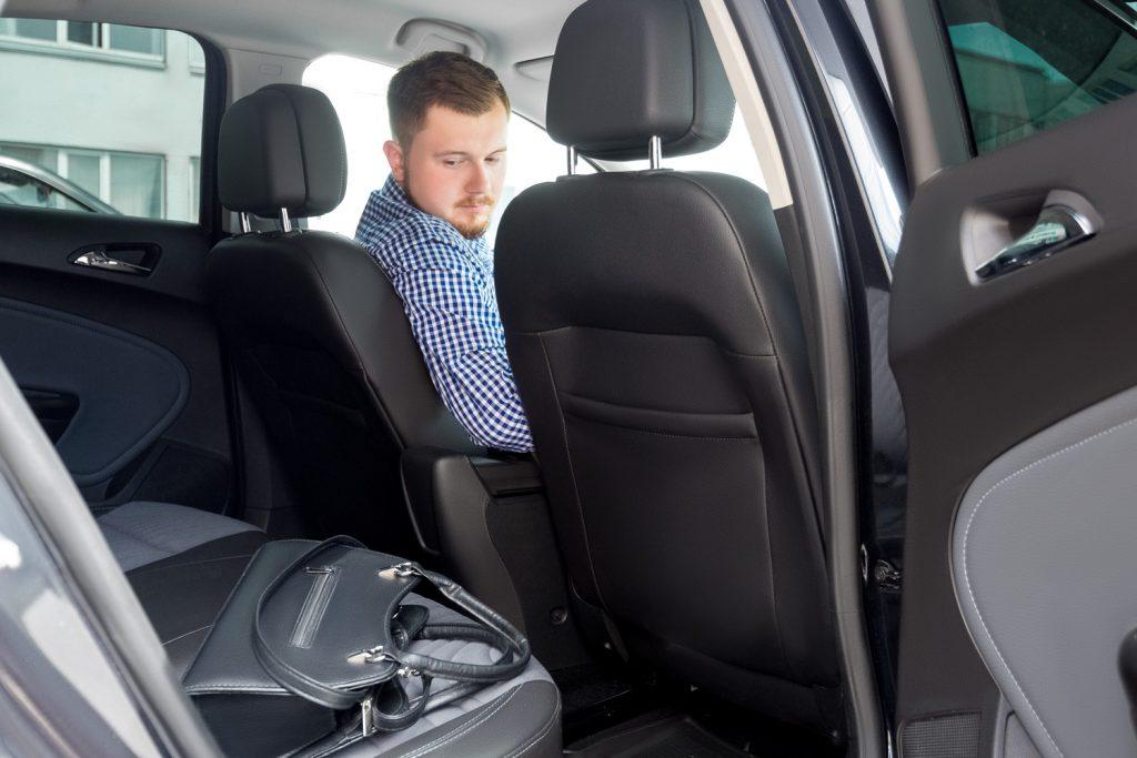 Мужчина смотрит на забытую вещь пассажиром