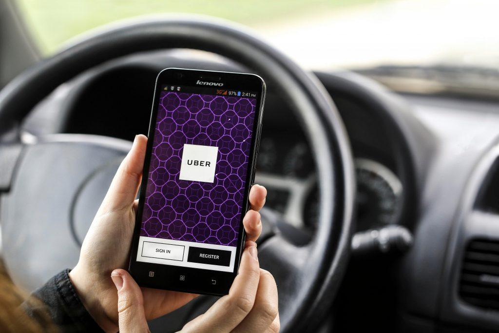 Женщина в машине держит мобильный телефон
